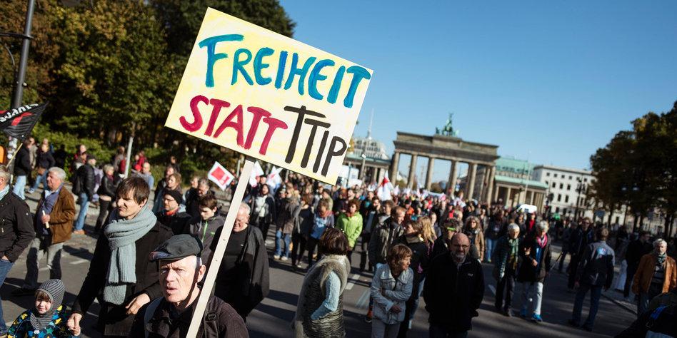 """Ein Mann trägt am 10.10.2015 ein Schild mit der Aufschrift """"FREIHEIT STATT TTIP"""" auf einer Demonstration gegen das transatlantische Handelsabkommen TTIP (USA) und Ceta (Kanada) auf der Straße des 17. Juni in Berlin. Organisiert wird die Protestaktion unter anderem von Umwelt-, Sozial-, Kultur- und Verbraucherverbänden, darunter der BUND und der Deutsche Gewerkschaftsbund (DGB). Foto: Gregor Fischer/dpa +++(c) dpa - Bildfunk+++"""