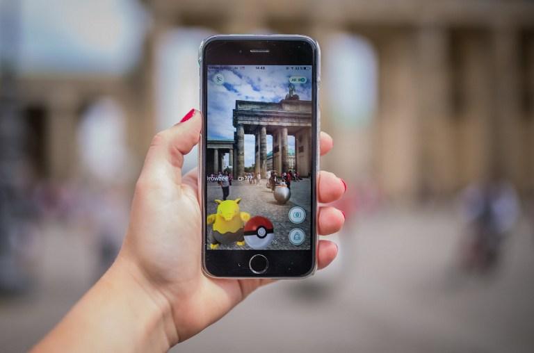 Eine Frau, die am Brandenburger Tor in Berlin Pokémon Go spielt.