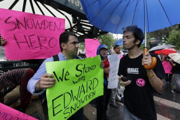 Demonstrators hold signs supporting Edward Snowden in New York's Union Square Park, Monday, June 10, 2013. Snowden, who says he worked as a contractor at the National Security Agency and the CIA, gave classified documents to reporters, making public two sweeping U.S. surveillance programs and touching off a national debate on privacy versus security. (AP Photo/Richard Drew)
